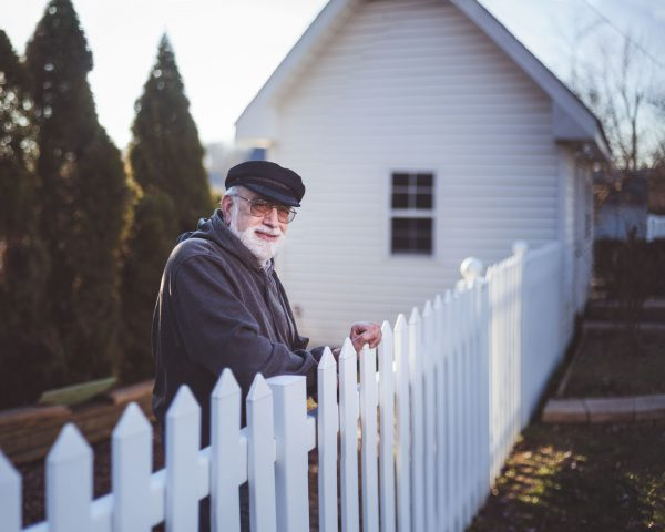 man leaning on a fence